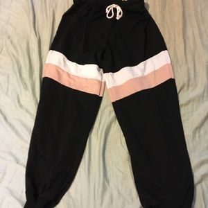 Black sweatpants with pink and white stripes